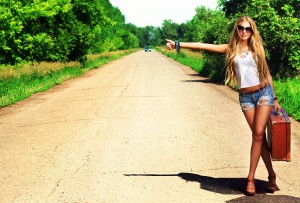12521834 - pretty young woman hitchhiking along a road.